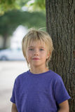 Portrait of a young boy in front of a tree stock photo