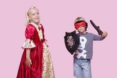 Portrait of young boy and girl in stage costume over pink background Stock Photos