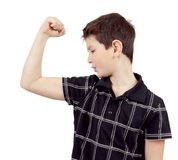 Portrait of a young boy with hand raised up and showing muscles Royalty Free Stock Photography