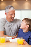 Portrait of a young boy and his father having breakfast Stock Photography