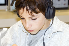Portrait of a young boy listening to music on head. Portrait of a sweet young boy listening to music on headphones Royalty Free Stock Photography