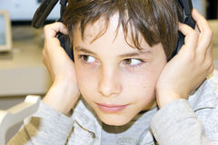 Portrait of a young boy listening to music on headphones. Portrait of a sweet young boy listening to music on headphones Stock Photos