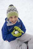 Portrait of young boy making snowball Royalty Free Stock Photos