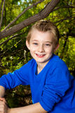 Portrait of a Young Boy in Nature. A young boy sits in a wooded area and smiles for a portrait.  He has blond hair and blue eyes and is wearing a bright blue Stock Image