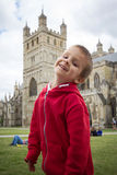 Portrait of a young boy in the park, cathedral in Exeter, Englan Stock Photo