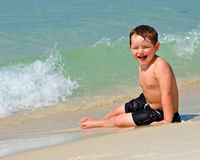Portrait of young boy playing in surf at beach Royalty Free Stock Images