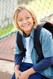 Portrait Of Young Boy With Rucksack Sitting In Park Royalty Free Stock Image