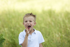 Portrait of young boy shouting loudly on summer day Royalty Free Stock Photo