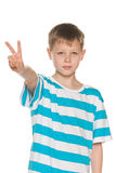Young boy shows victory sign Royalty Free Stock Photography