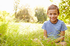 Portrait of a young boy sitting outdoors on a sunny day Stock Photography