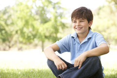Portrait Of Young Boy Sitting In Park Stock Photos
