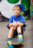 Portrait of Young Boy Sitting on Skateboard Royalty Free Stock Photos