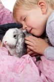 Portrait of a scandinavian young boy in studio with a rabbit stock photo