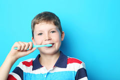 Young boy with toothbrush. Portrait of young boy with toothbrush on blue background stock photo