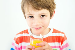 Portrait of a young boy who is drinking juice in the white background. Stock Image