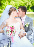 Portrait of young bride and groom kissing on sunny day outdoors Stock Photo