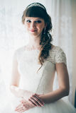 Portrait of a young bride standing near  window. Portrait of a young bride standing near a window Royalty Free Stock Photography