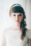 Portrait of a young bride standing near  window. Portrait of a young bride standing near a window Royalty Free Stock Photo