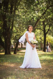Portrait of a young bride with  wedding bouquet on  park backgro Royalty Free Stock Photos