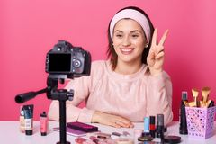 Portrait of young brunette blogger taking video via digital camera and showing peace sign. Cheerful model posing in studio on pink stock photos