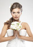 Portrait of a young brunette bride holding flowers Royalty Free Stock Images