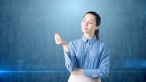 Portrait of young brunette business woman looking to her hand and thinking stock image
