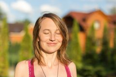 Portrait of young brunette caucasian woman smiling with closed eyes outdoors. Golden hour sunlight at sunset.  Gree Stock Photo