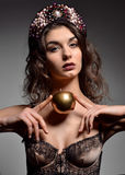 Portrait of young brunette fashion woman with gold apple Stock Photography