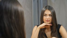 Portrait of a young brunette girl is looking in the mirror putting her hand to the chin stock photos