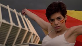 Portrait of a young brunette girl soccer fan in Spain, looking at the camera, serious face, holding a flag behind her stock footage
