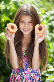 Portrait of a young brunette little girl with peach Royalty Free Stock Photography
