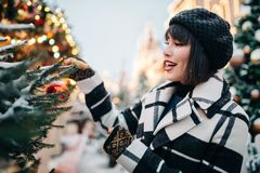 Portrait of young brunette near painted Christmas tree on street stock photography