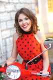 Portrait of a young brunette on an old red scooter Stock Image