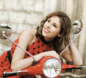 Portrait of a young brunette on an old red scooter Stock Photography