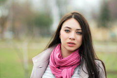 Portrait of young brunette. With pink scarf posing outside Stock Photography
