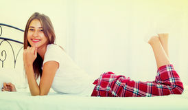 Portrait of young brunette posing in home bed Royalty Free Stock Images