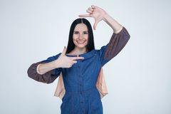 Portrait of young brunette positive female with cheerful expression, dressed in jeans dress, has good mood, gestures actively at royalty free stock images