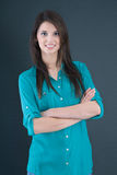 Portrait of a young brunette pretty girl in a green blouse. Stock Photo