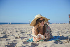 Portrait of a young brunette relaxing on the beach, reading a bo Stock Images