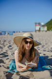 Portrait of a young brunette relaxing on the beach, reading a bo Royalty Free Stock Photo