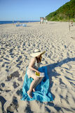 Portrait of a young brunette relaxing on the beach, reading a book Royalty Free Stock Image
