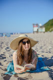 Portrait of a young brunette relaxing on the beach, reading a book Stock Photo