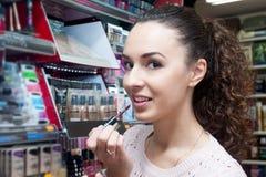 Brunette selecting lip gloss Stock Photos