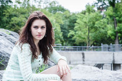 Portrait of young brunette sitting on the bouders Royalty Free Stock Photos