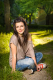 Portrait of  young brunette sitting in the park Royalty Free Stock Image