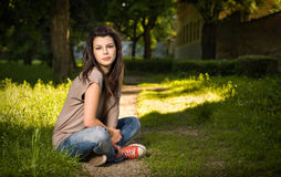 Portrait of young brunette sitting in the park Stock Photo