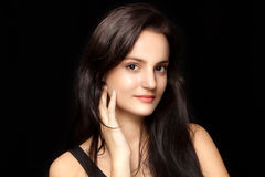 Portrait of a young brunette with soft skin on a black backgroun Stock Photos