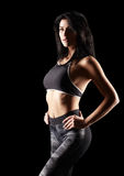 Portrait of a young brunette sporty fitness woman on black Royalty Free Stock Images