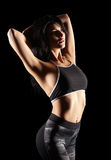 Portrait of a young brunette sporty fitness woman on black Stock Photo