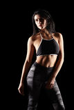 Portrait of a young brunette sporty fitness woman on black Stock Photography